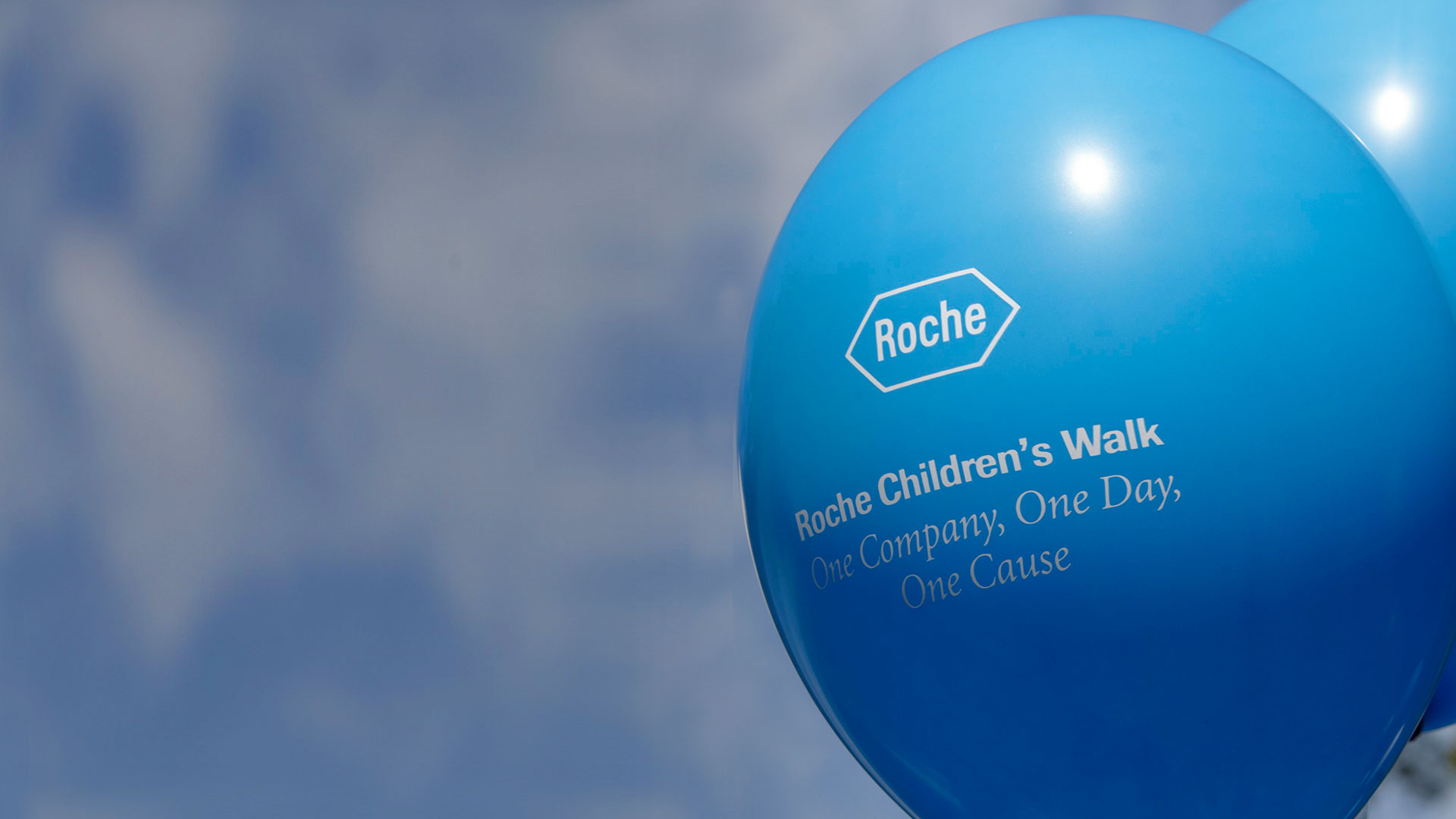 "Blue balloon with script ""Roche Children's Walk"" in front of a blue sky"