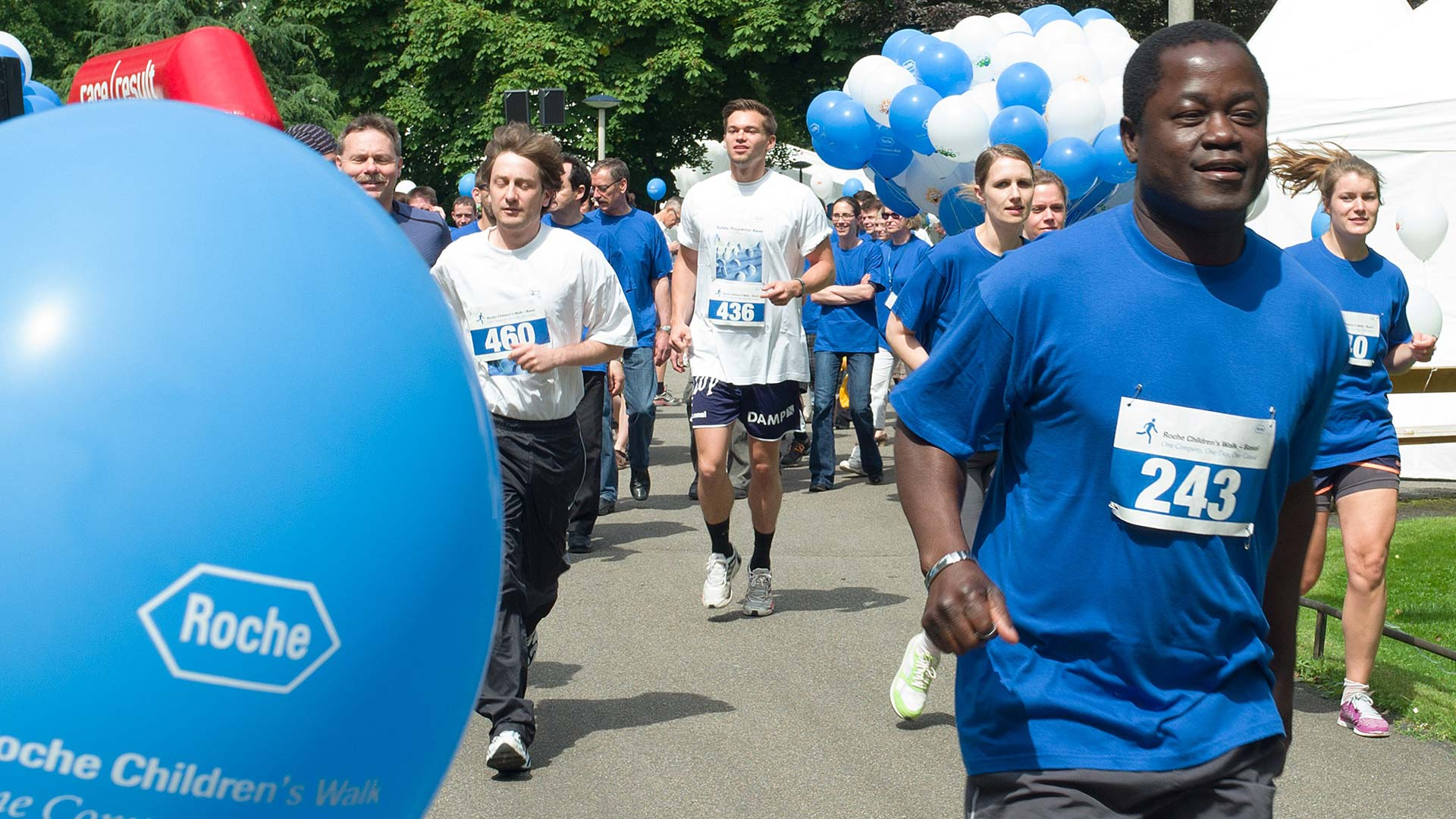 Roche employees wearing blue and white Roche t-shirts participating in a running event for the children's walk