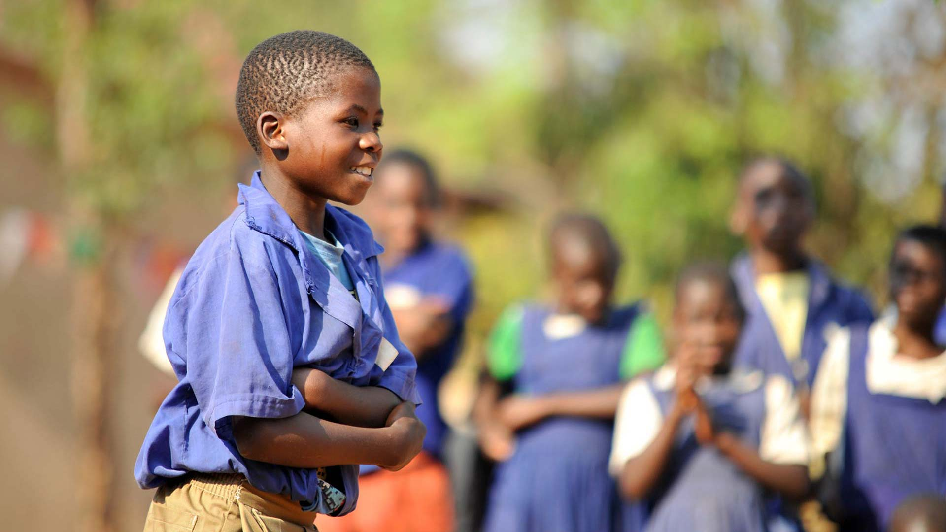 Malawian child hugging himself and smiling with more children in the background