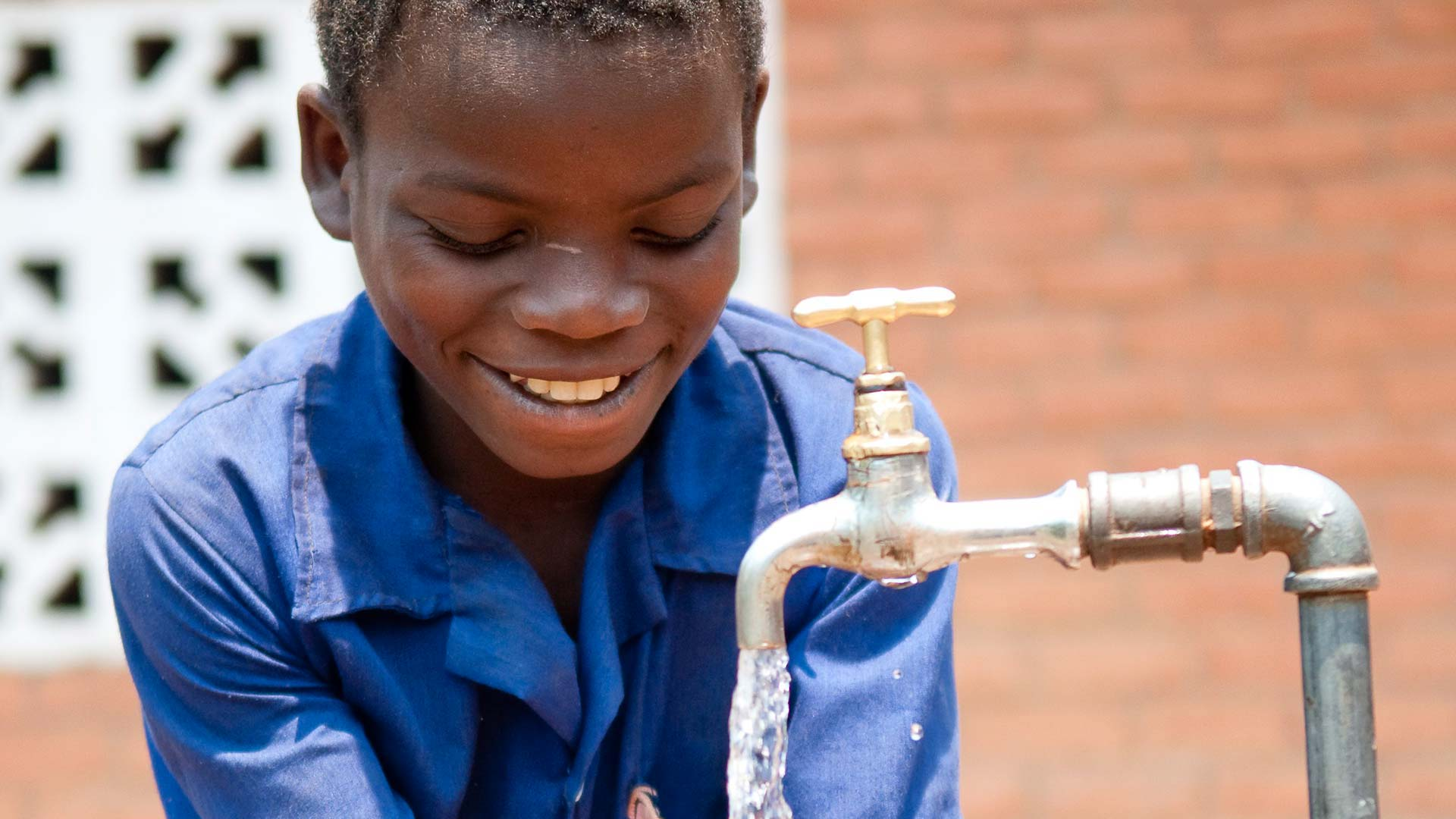 Malawian child smiling at water from a flowing tap