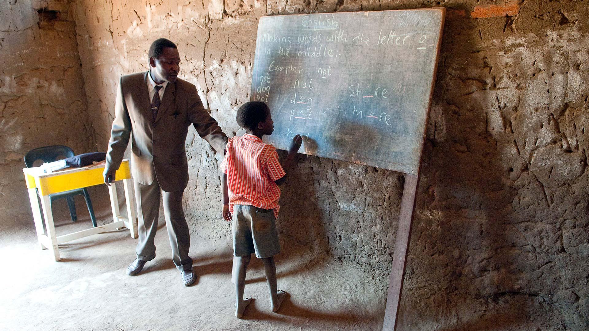 Malawian teacher has child writing English on a blackboard in a classroom