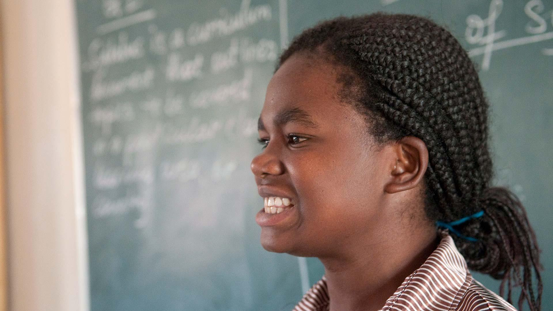 Malawian child talking to class in front of blackboard