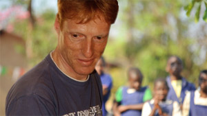Roche employee Daniel Indergand in Malawi with Malawian children in the background