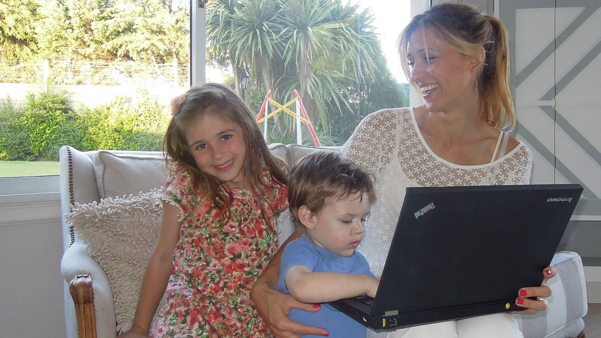 Jessica Claros at her laptop with her children