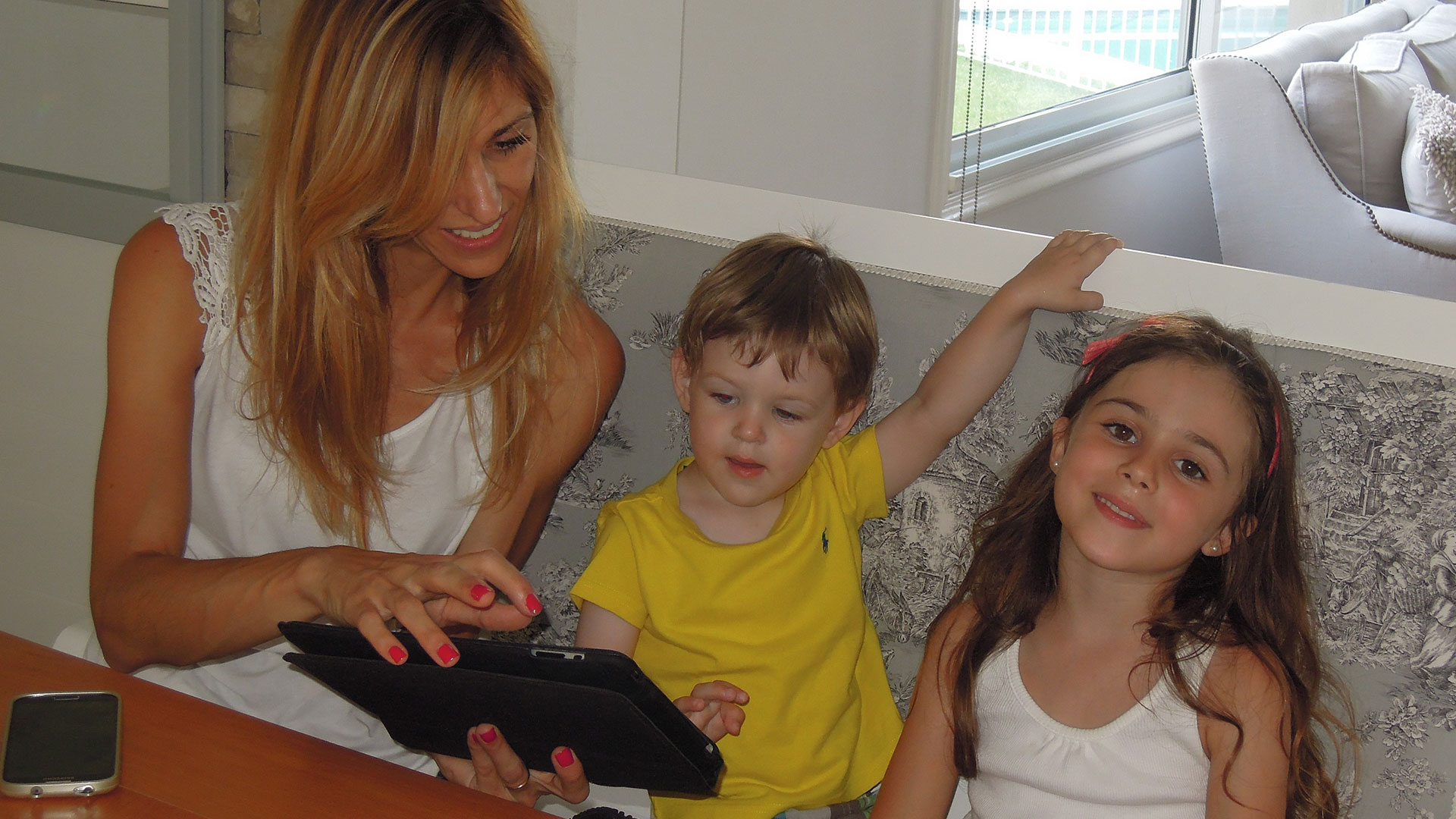Jessica Claros at her tablet with her children