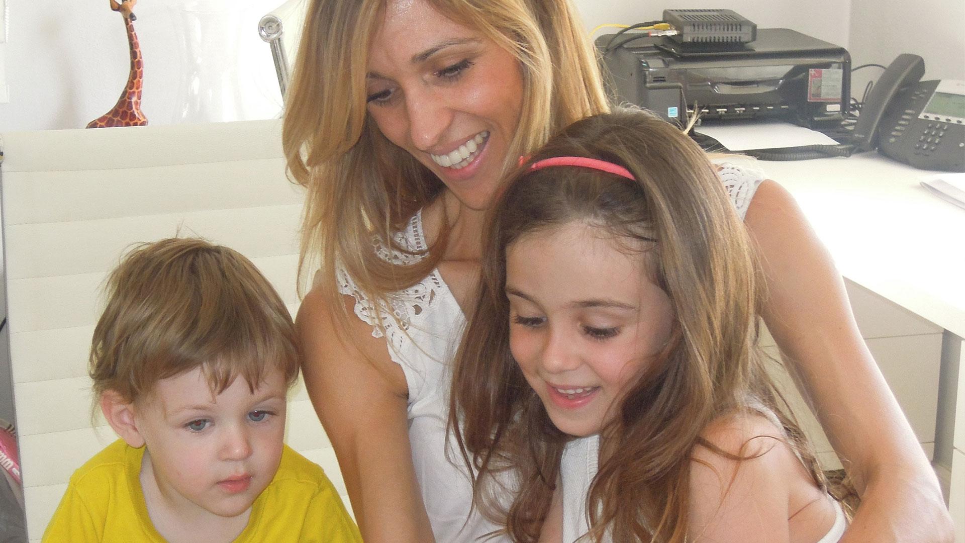 Jessica Claros at her desk with her children