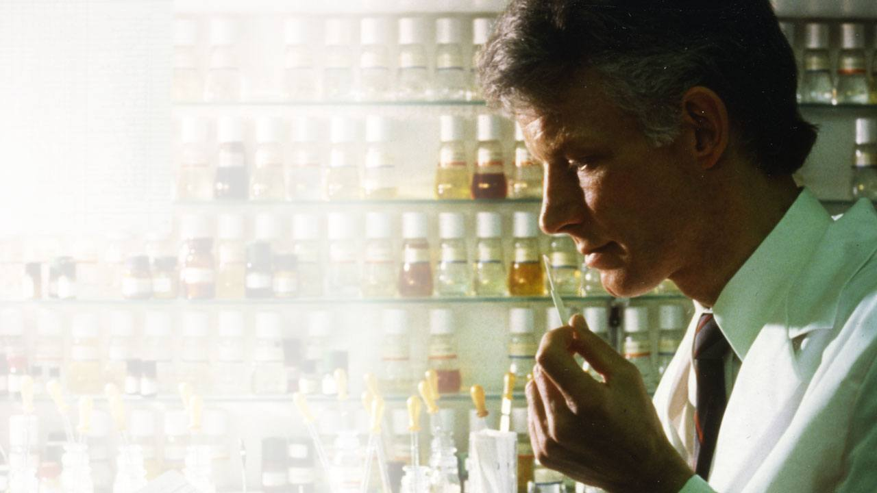 Male researcher smelling perfume strip