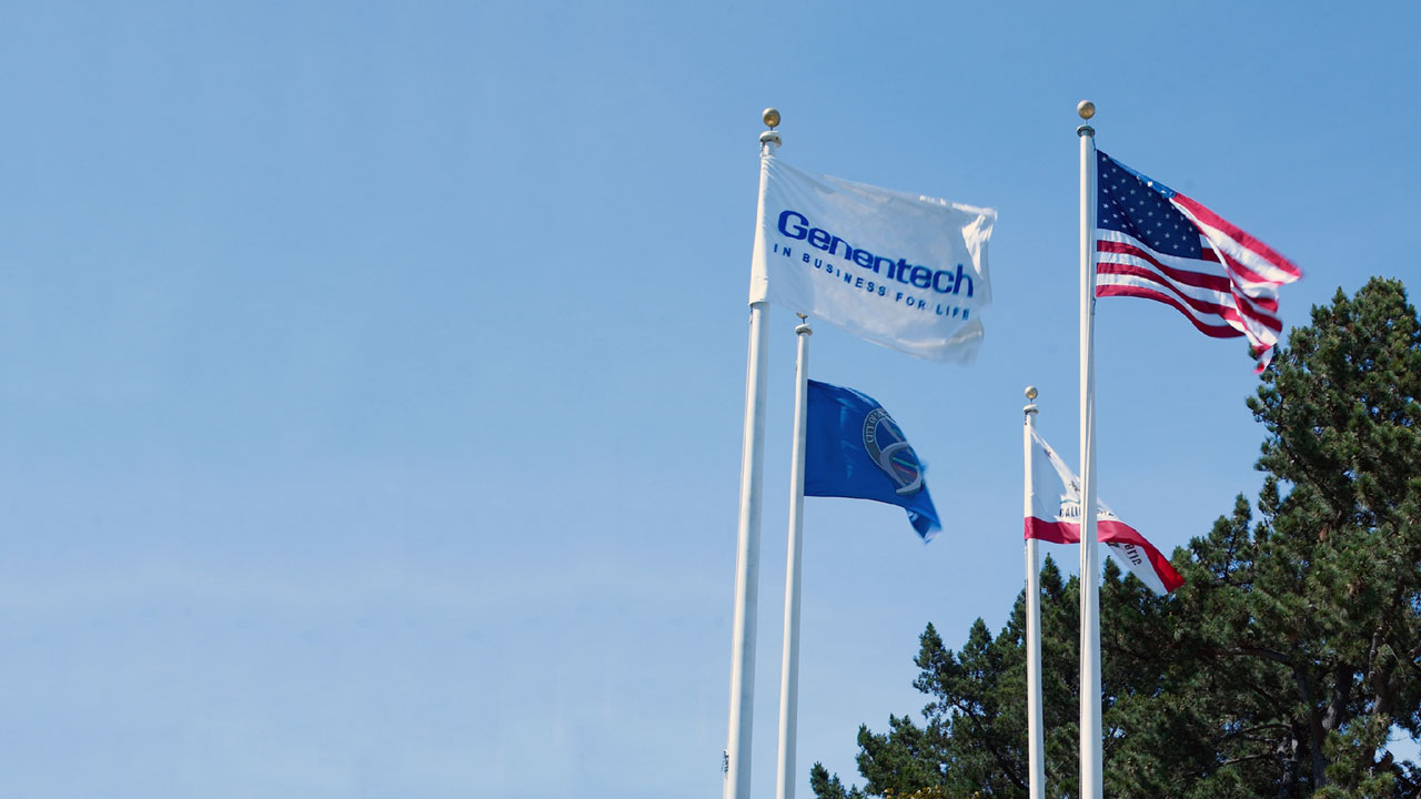 Genentech flag flying next to an American flag