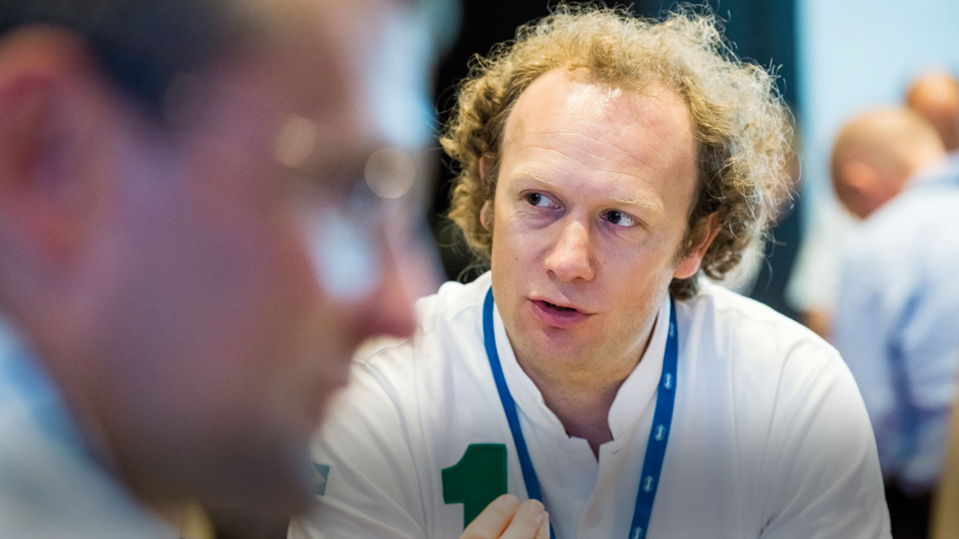 Dr Andrew Thomas talking to a colleague at a conference