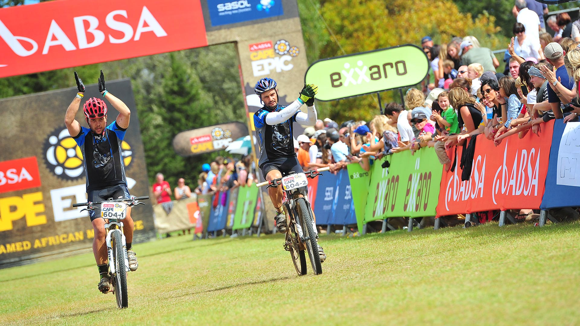 A man and Coen van Tonder after the finishing line clapping at the audience of the Cape Epic race while riding their mountain bikes