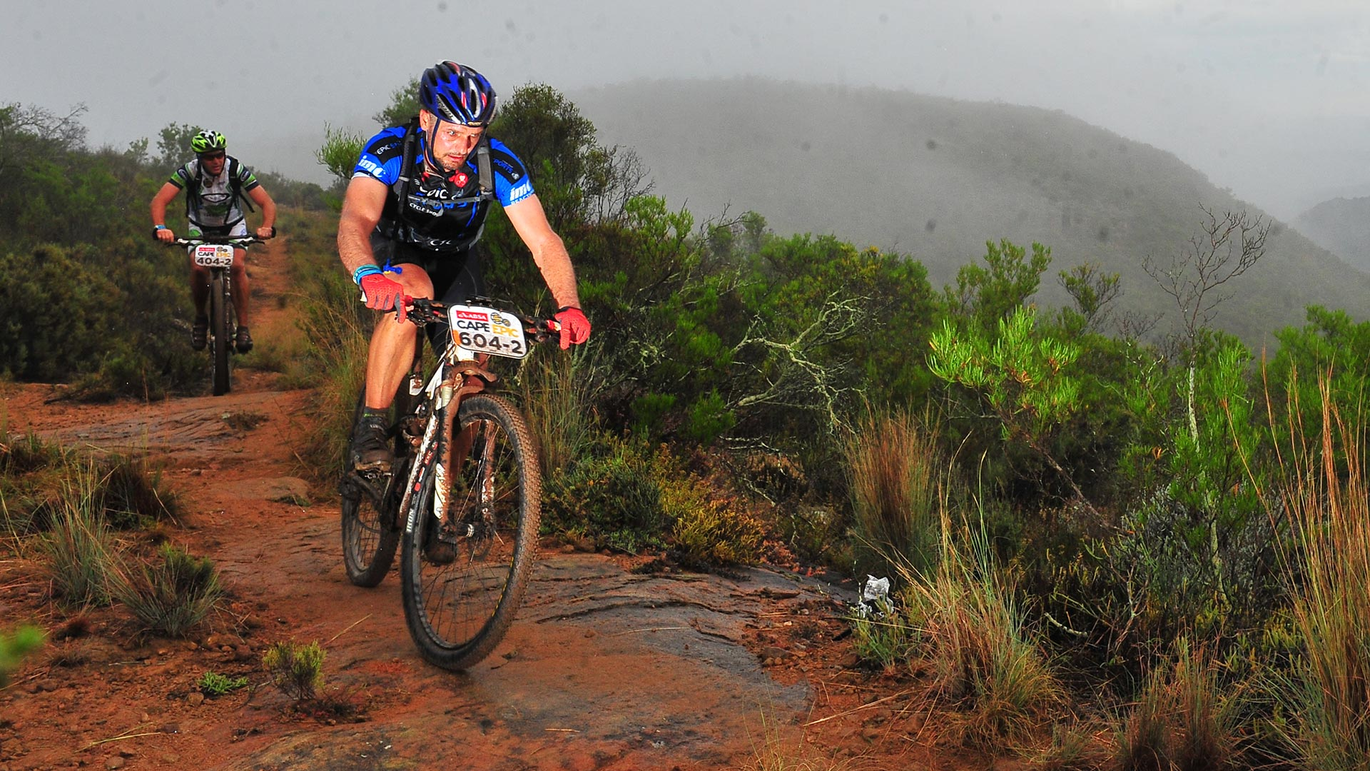 Coen van Tonder pursued by another contestant riding his mountain bike down a muddy course