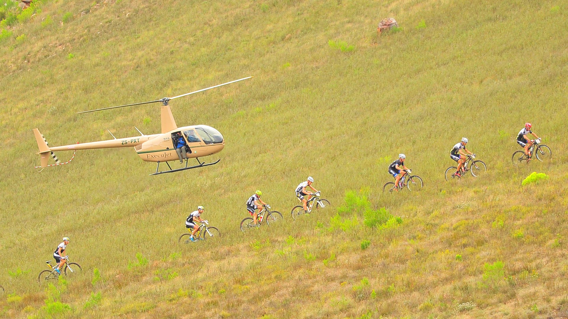A helicopter with a camera team hovering over a group of mountain bikers who cross grassland