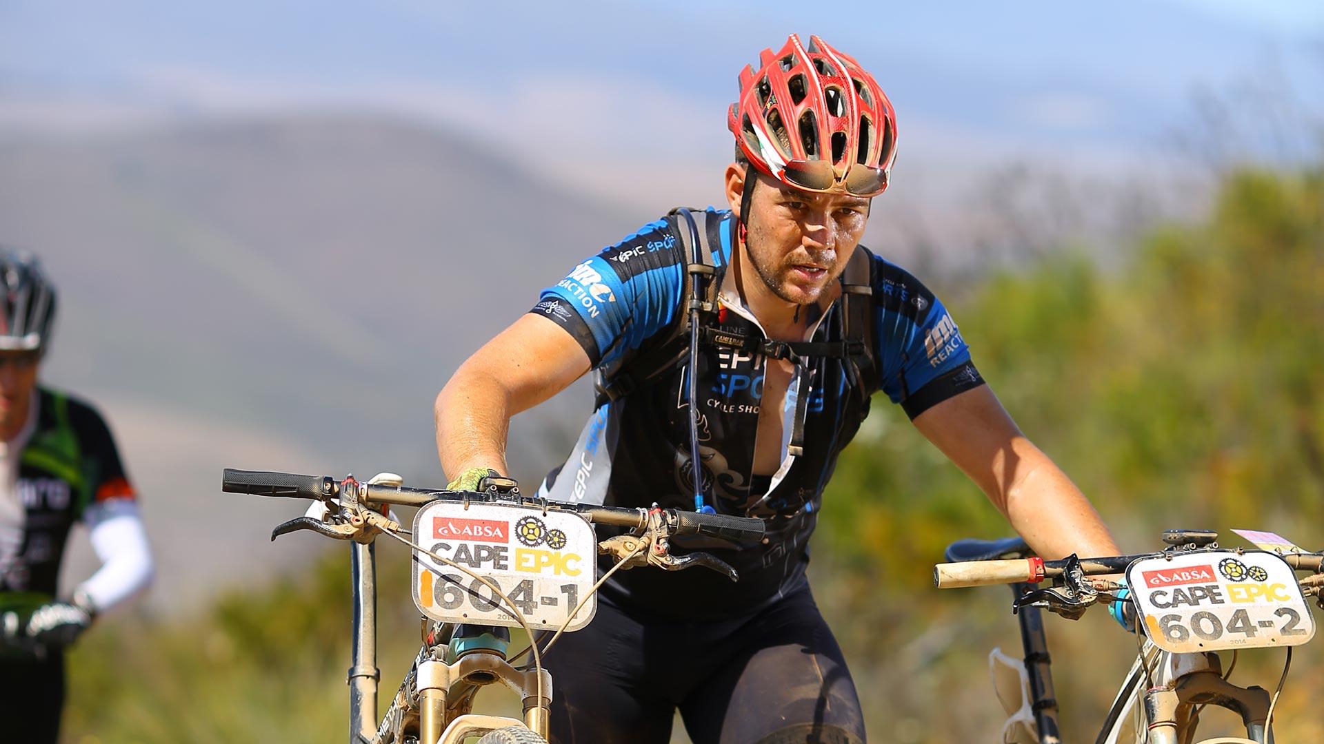 Coen van Tonder pushing two mountain bikes