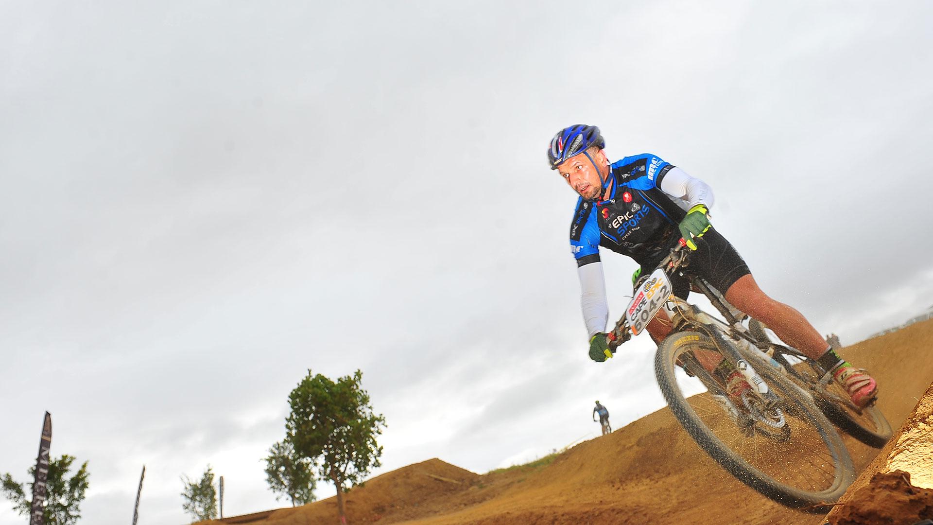 Coen van Tonder riding a mountain bike down a sandy slope