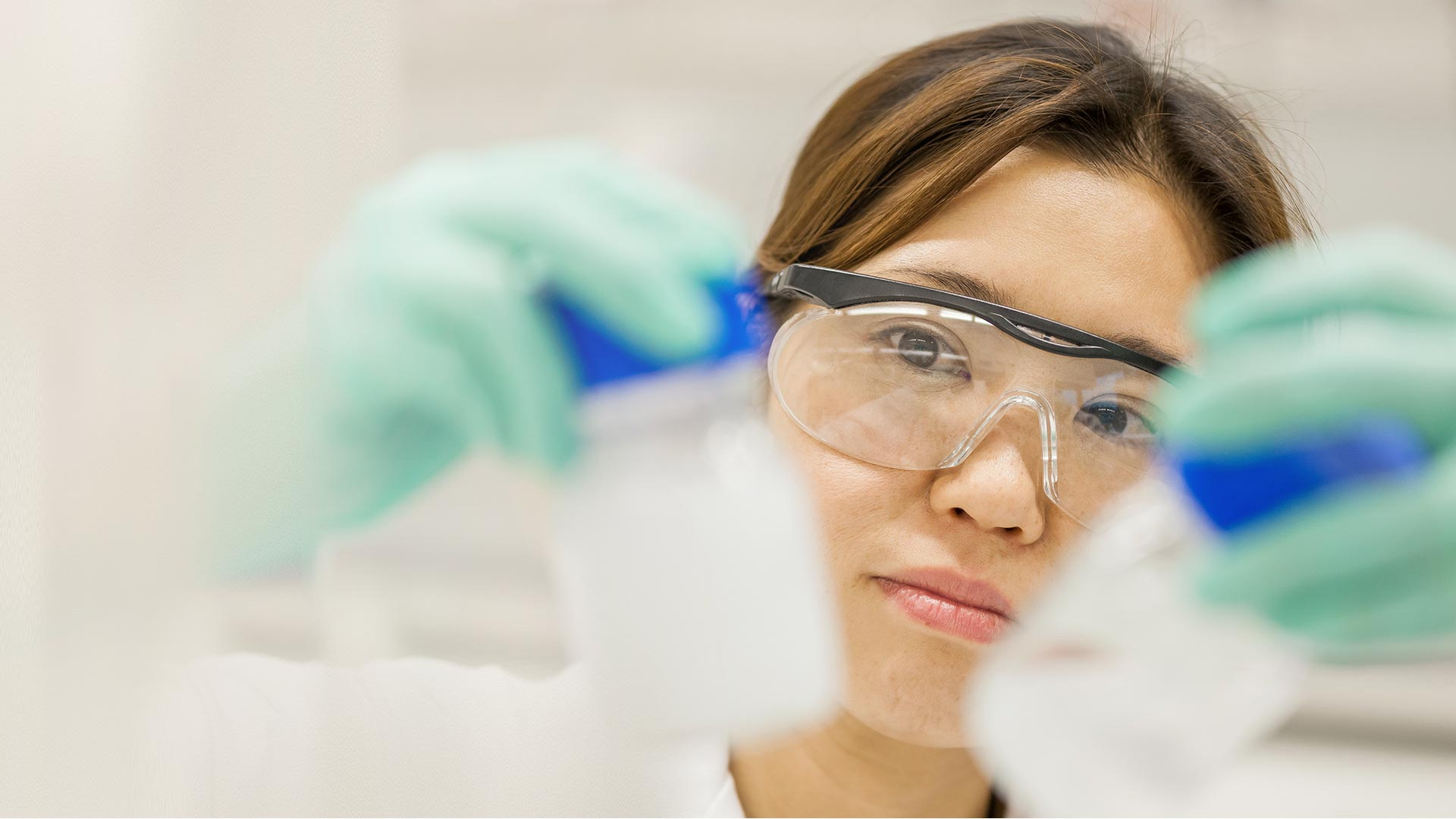 Female researcher wearing goggles and gloves, inspecting samples